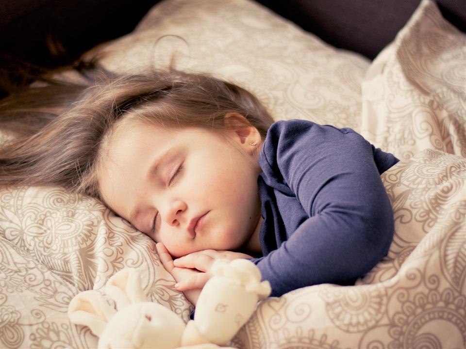 здоровый сон ребенка, девочка спит в кровати с игрушкой