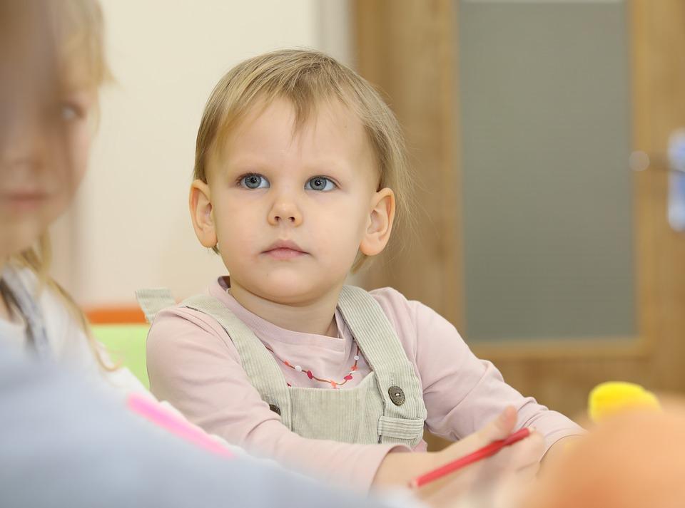 девочка с большими голубыми глазами сидит с карандашом и смотрит