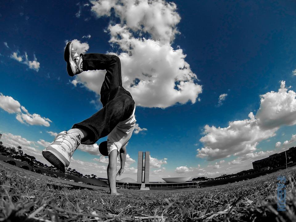 парень на траве делает акробатический элемент