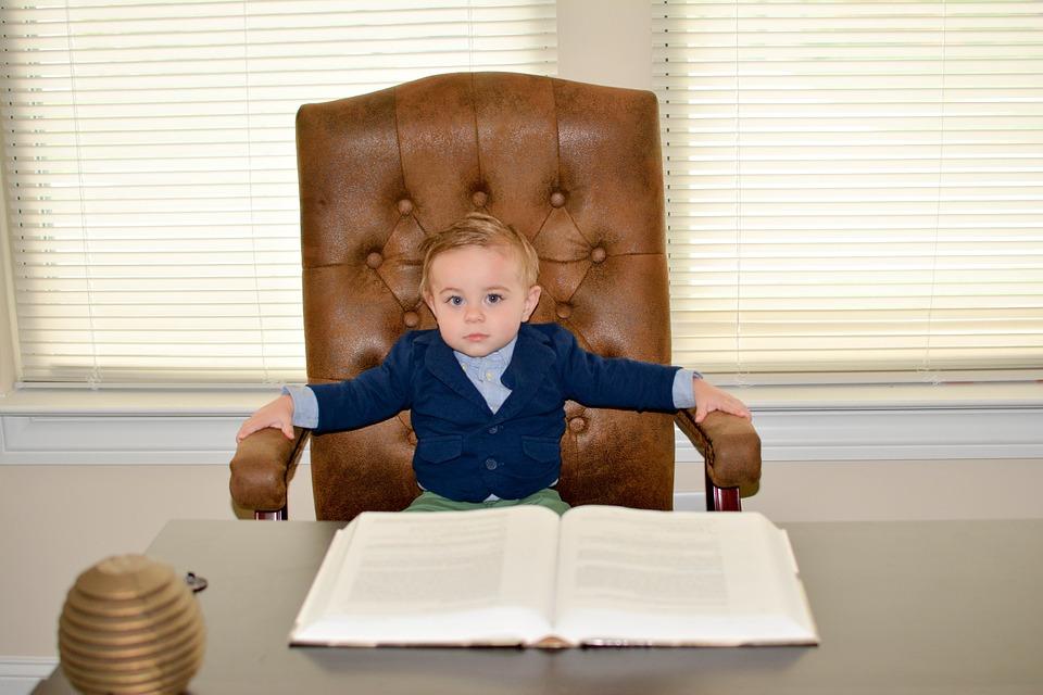 ребенок сидит в большом кожаном кресле за столом, здоровый сон ребенка
