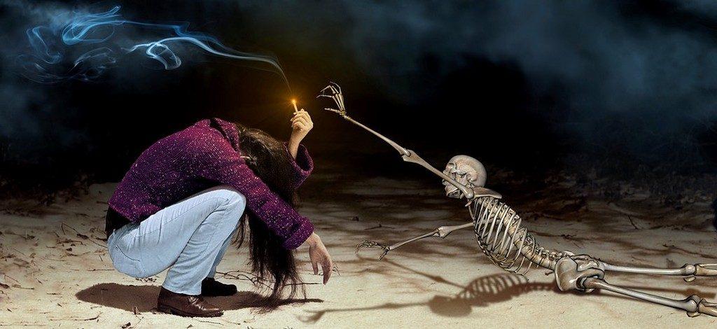 скелет тянется за сигаретой в руке у сидящего человека (вредные привычки и борьба с ними)