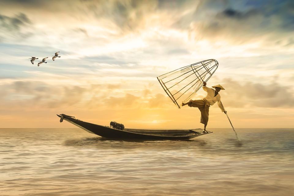 рыбак, стоя на лодке на одной ноге, ловит рыбу