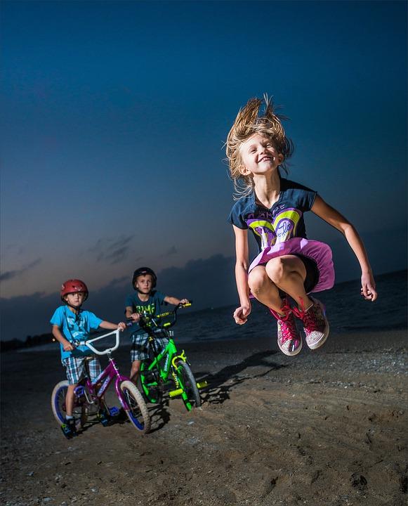 на берегу моря высоко прыгнула, а мальчики на велосипедах смотрят на нее