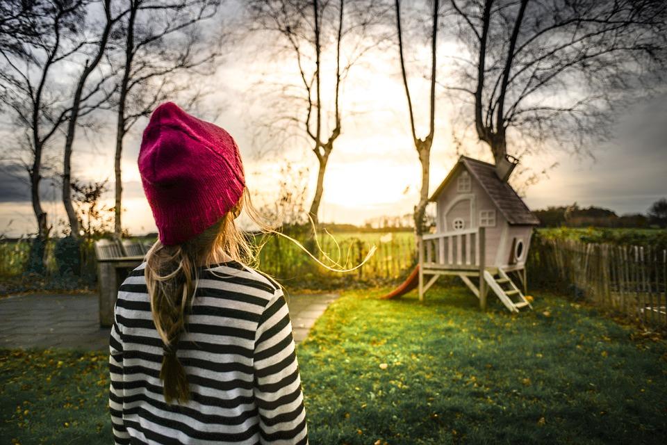 девочка в красной шапке смотрит на домик