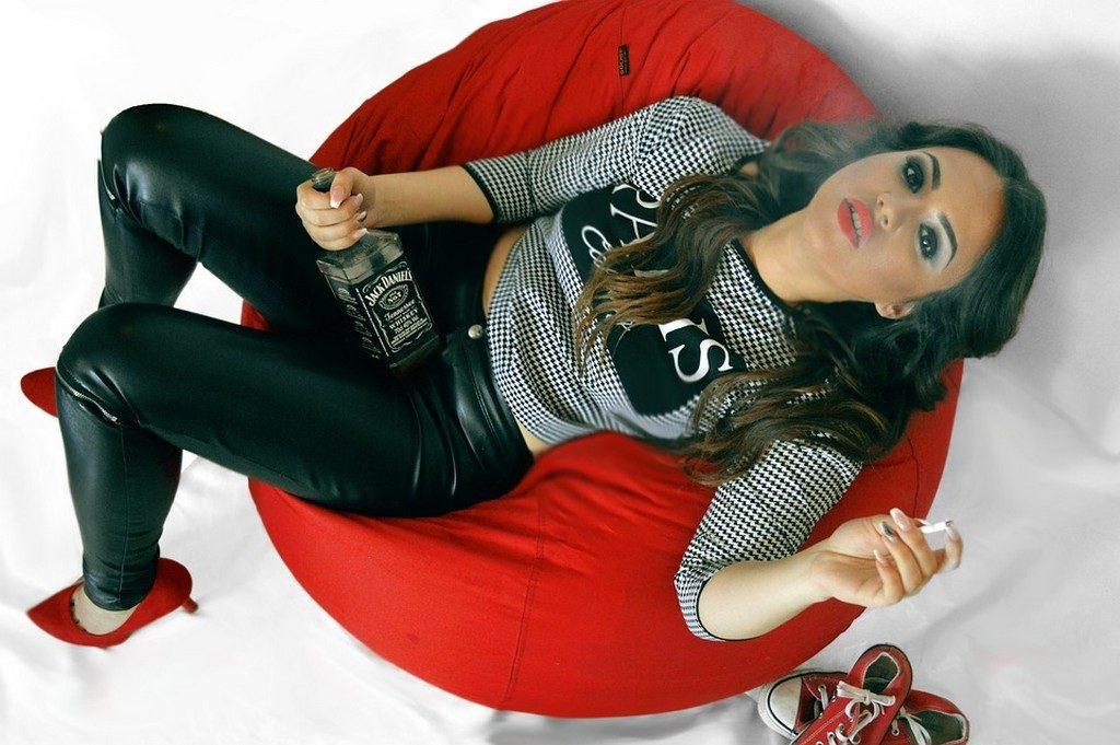Девушка сидит на диване держит в руке алкоголь и сигарету. Вредные привычки у подростков
