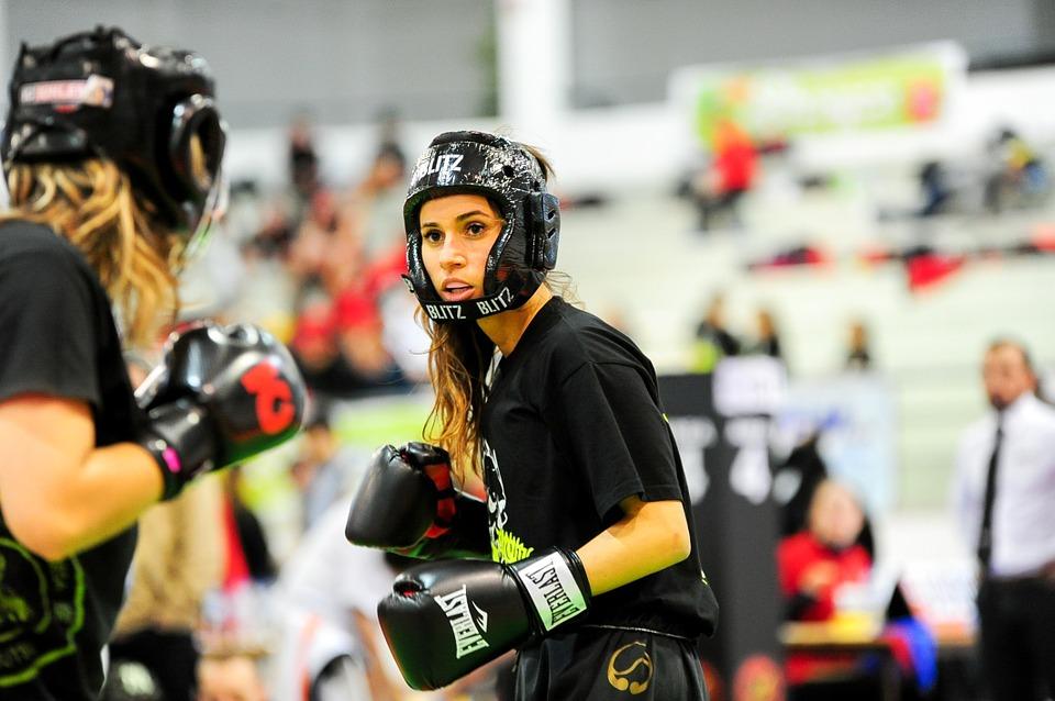 две девушки боксеры боксируют в шлемах и перчатках