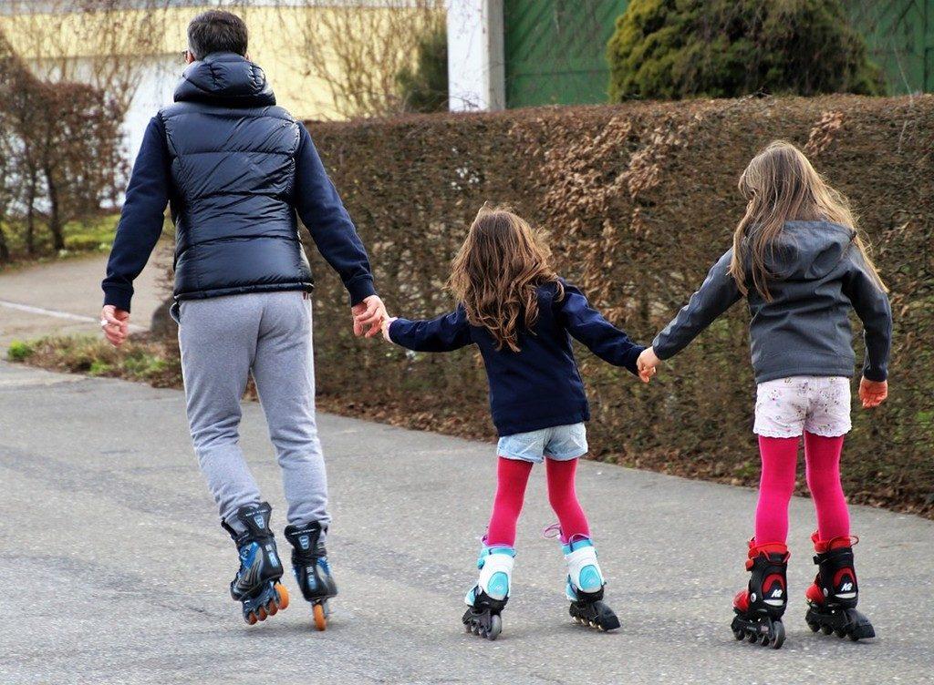 папа катается на роликах с двумя дочками