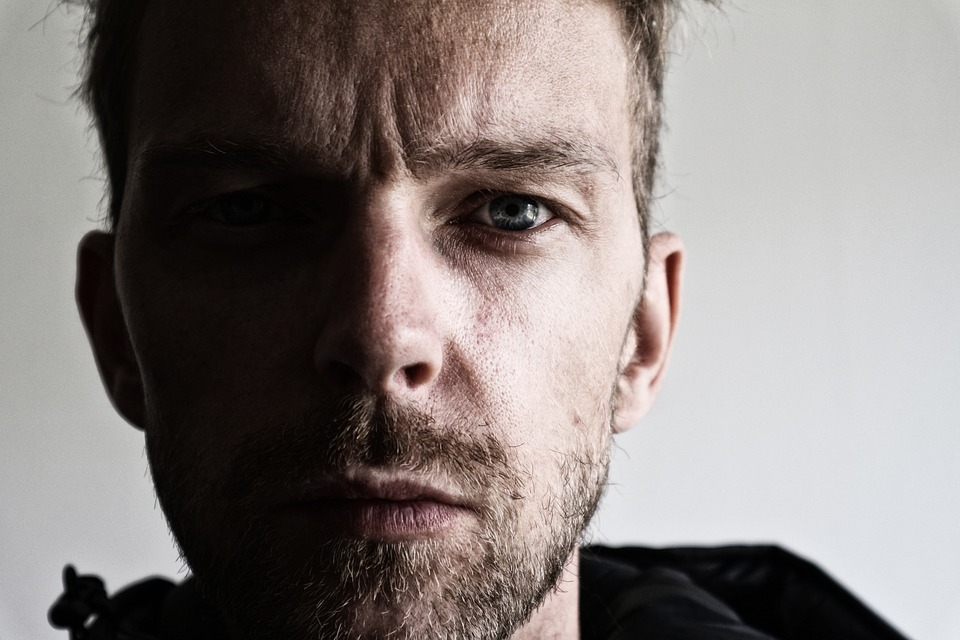 мужчина с серыми глазами смотрит прямо на зрителя