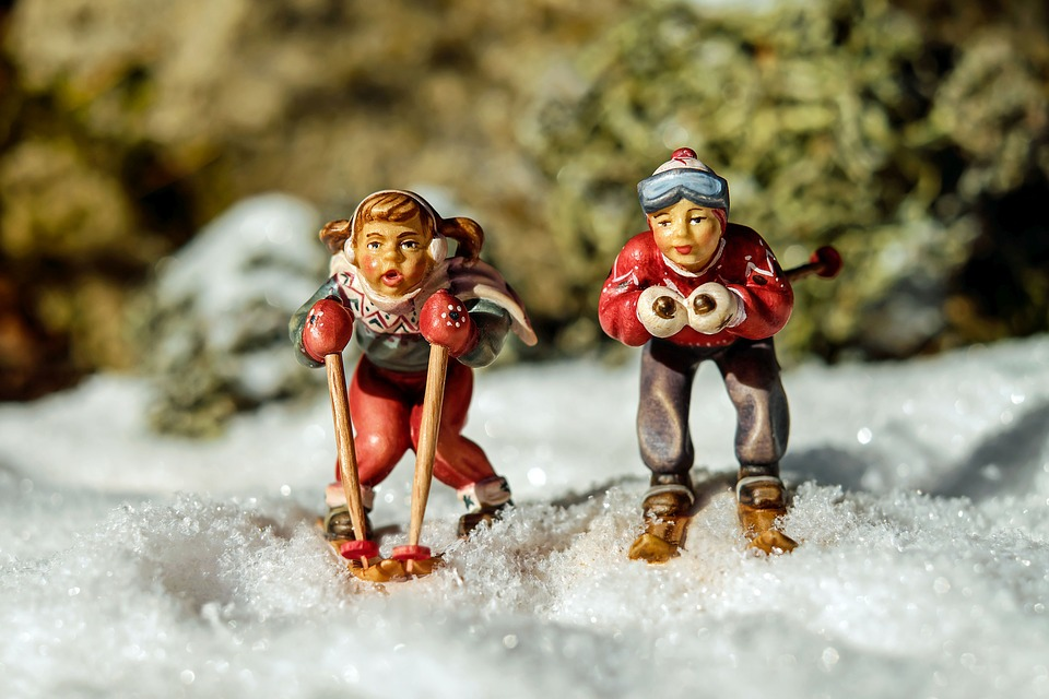 фигурки детей на лыжах стоят на снегу