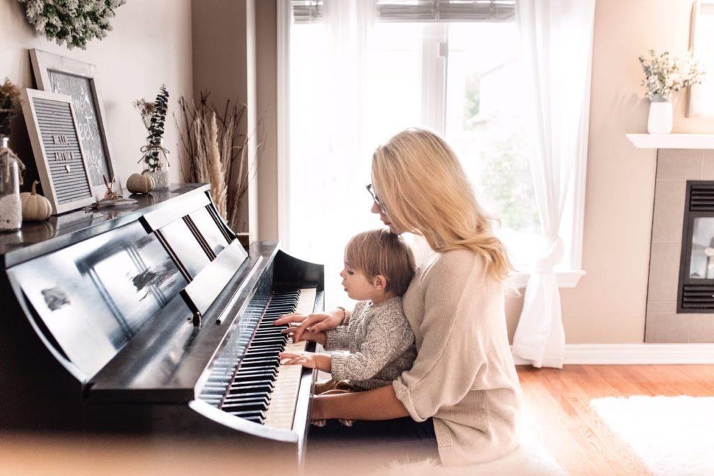 ребенок и мама играют на фортепьяно, ребенок сидит на коленях у девушки