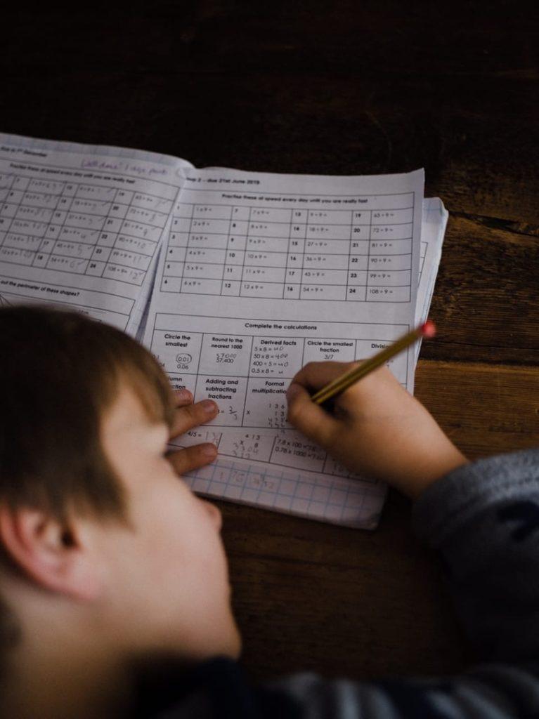 мальчик делает записи карандашом