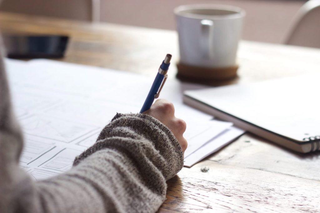 ребенок делает записи ручкой на рабочем столе