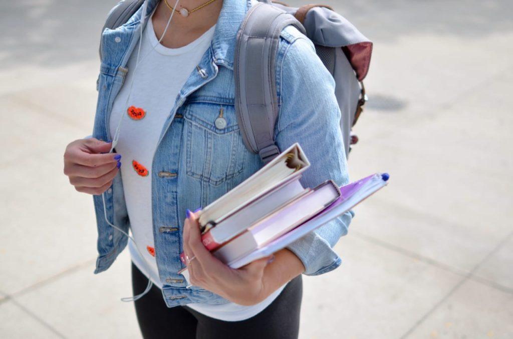 девушка с книгами в джинсовом жилете и с рюкзаком