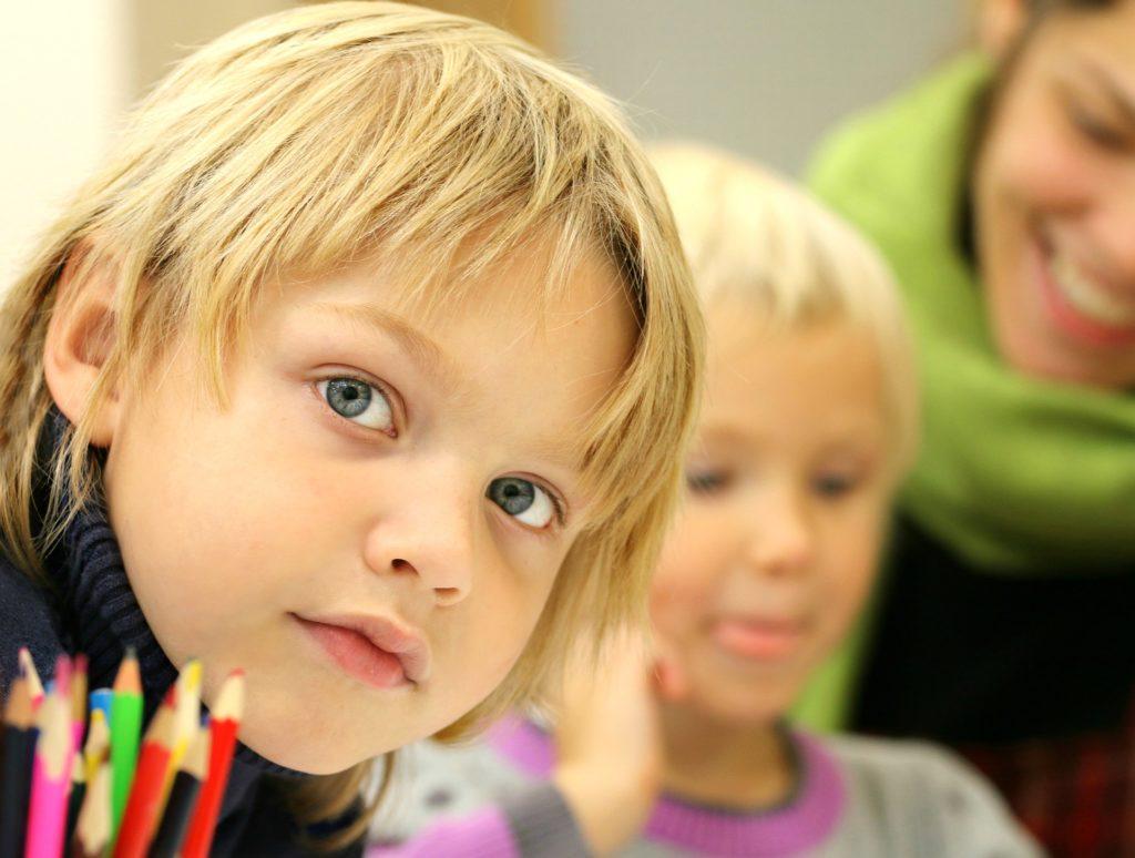 дети смотрят в камеру и цветные карандаши на переднем плане
