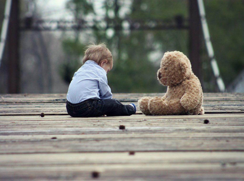 ребенок сидит на земле рядом с плюшевым медведем
