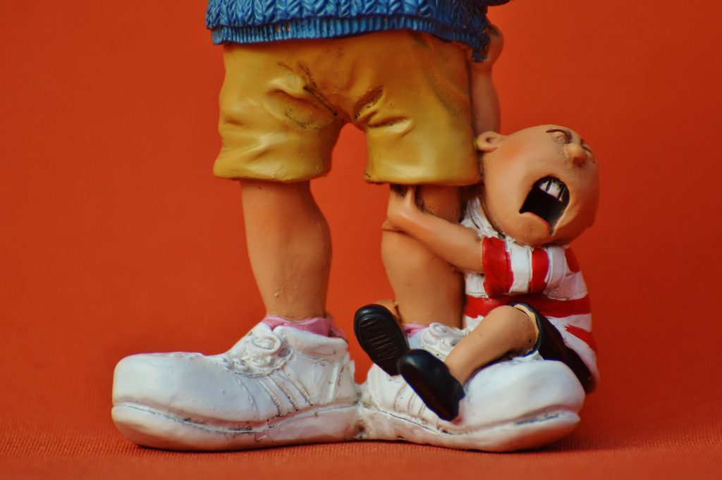 фигурка, где ребенок висит на ноге у отца и капризничает