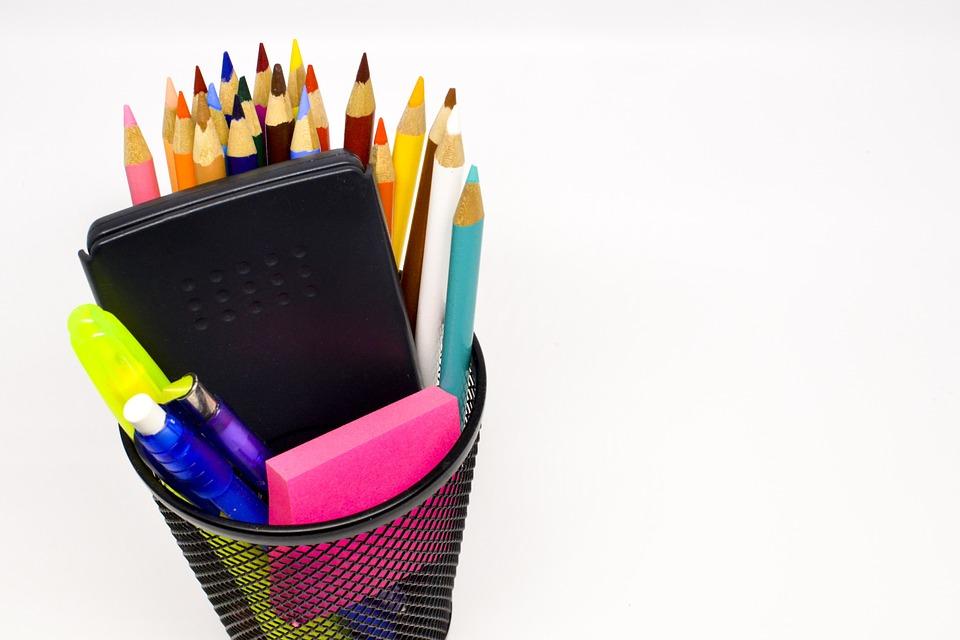стакан с канцелярскими товарами, цветные карандаши, ручки, калькулятор