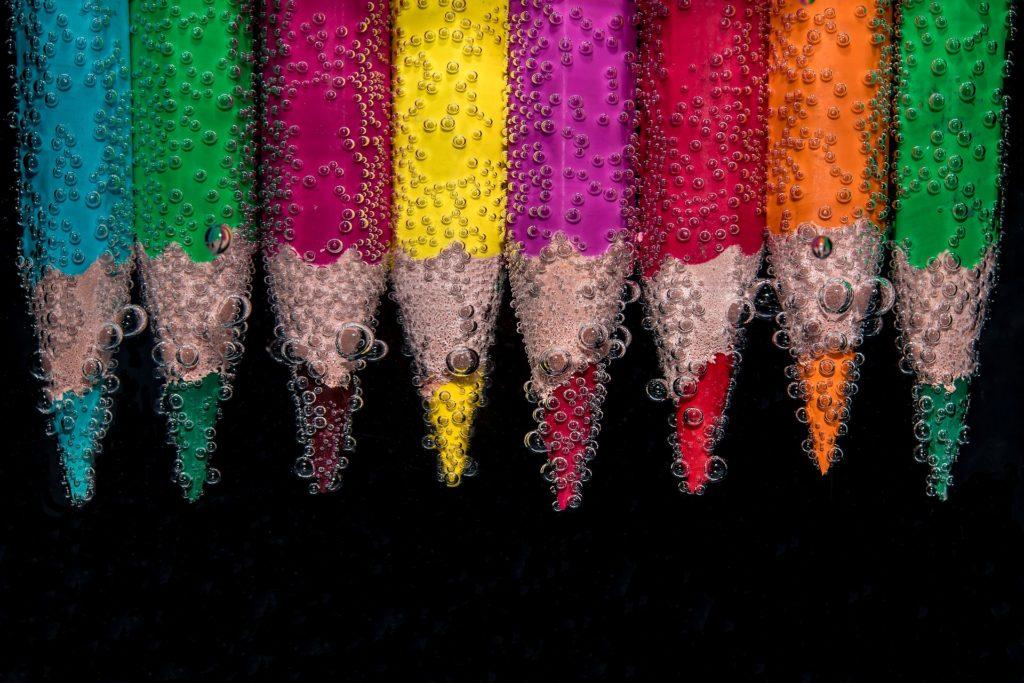 цветные карандаши, облепленные пузыриками воздуха