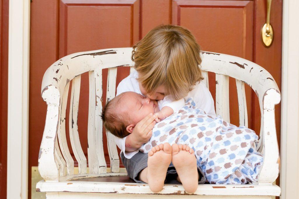 маленький ребенок держит грудного ребенка на коленях и касается своим носом носа младенца