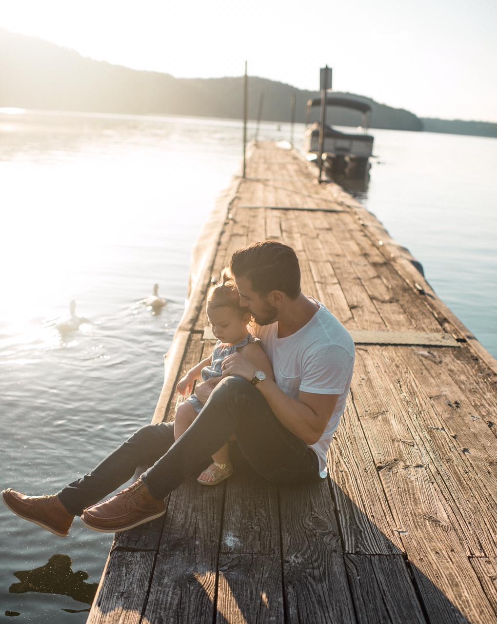мужчина сидит с ребенком на берегу озера