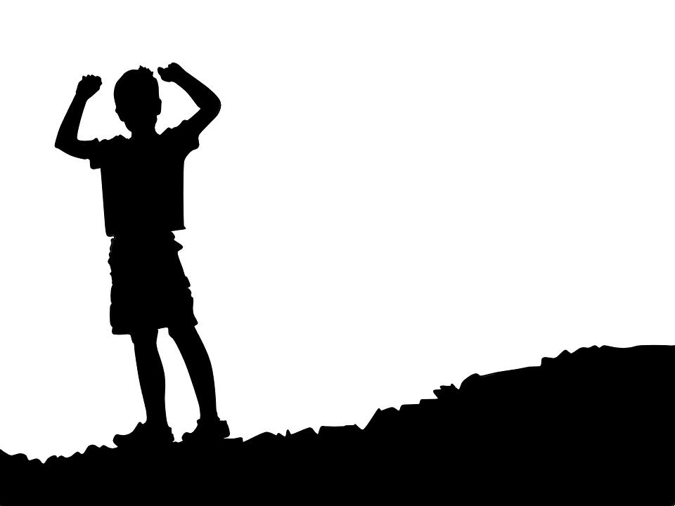 ребенок стоит на горе, подняв руки вверх