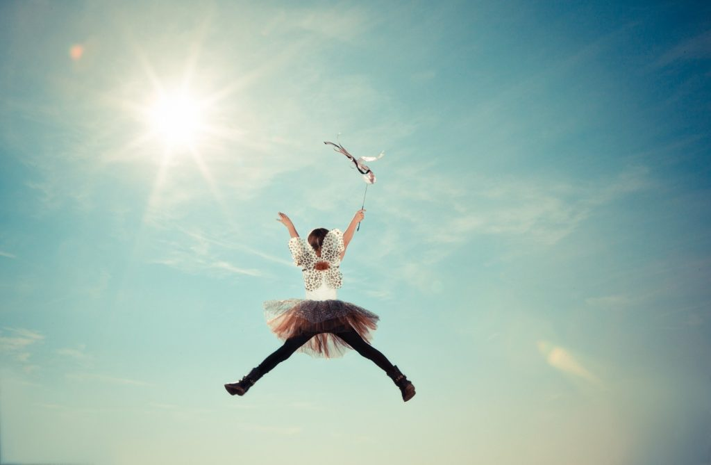 девочка в костюме феи прыгает на фоне неба