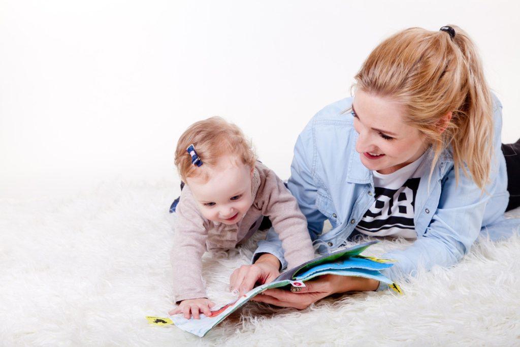 мама играет с ребенком, показывая книгу
