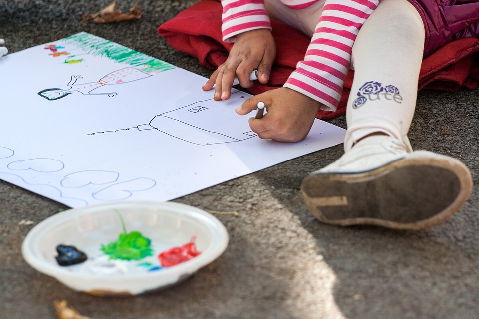 девочка сидя на асфальте рисует карандашами на бумаге