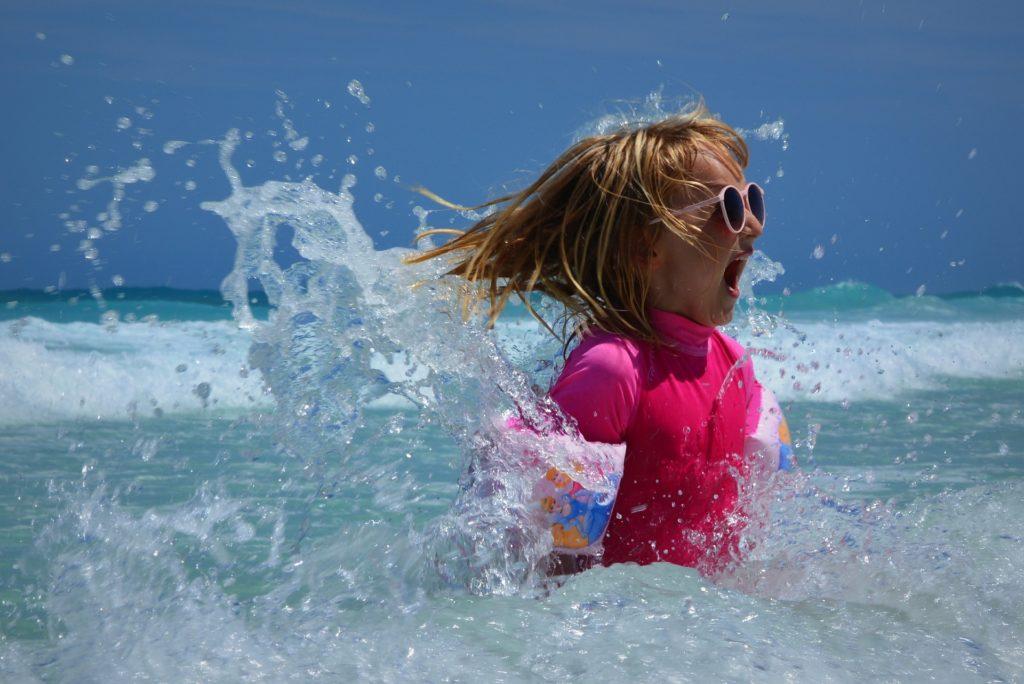 девочка в темных очках с бешенным выражением лица купается в море