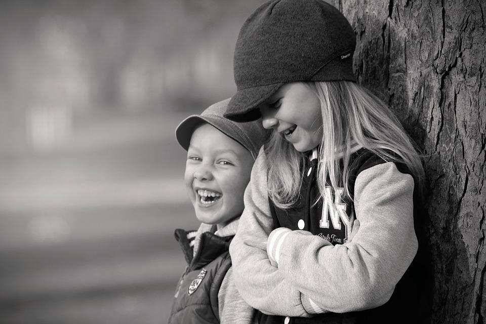 две девочки стоят и смеются стоя у стены