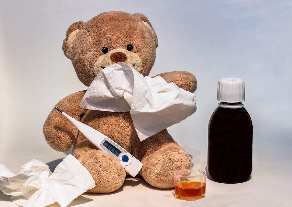 плюшевый медведь сидит с термометром, сиропом от кашля и салфетками, все это клинические проявленияя риновирусной инфекции