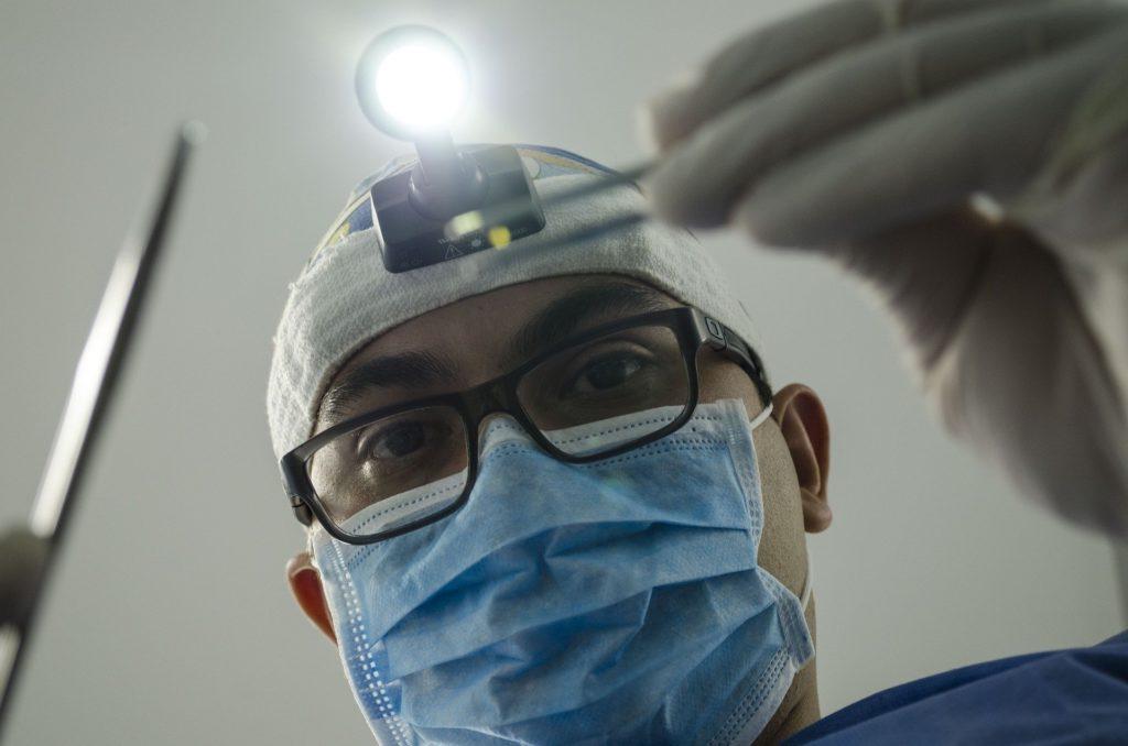 хирург делает операцию с фонариком на лбу