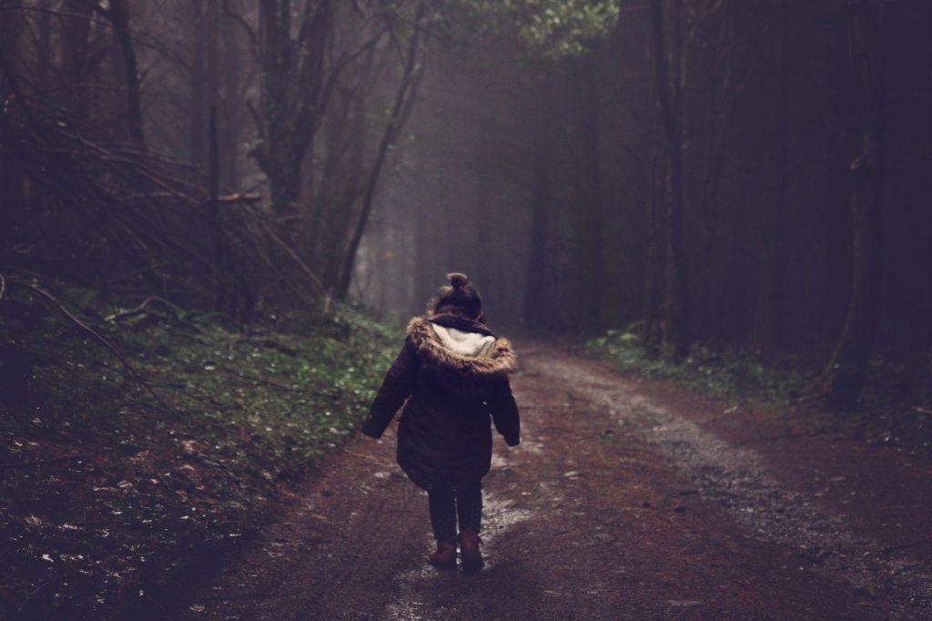 девочка идет по  дороге в пасмурную погоду