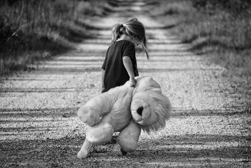 девочка грустная тащит плюшевого медведя