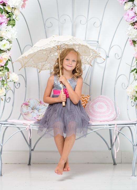 девочка с зонтиком сидит на скамейке