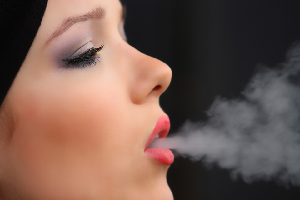 женщина выпускает дым изо рта