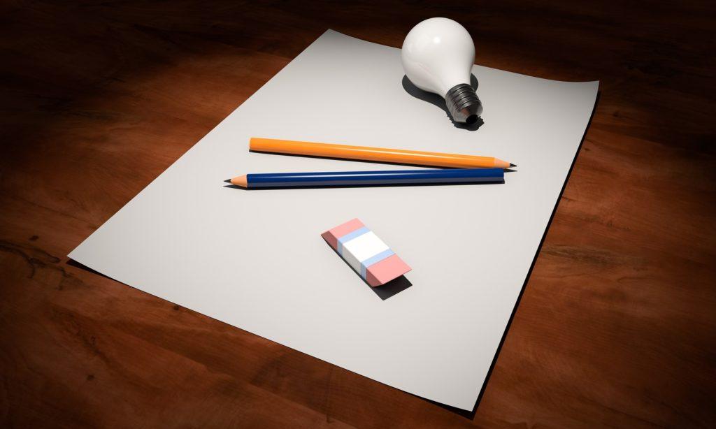 изображение ручки, карандаша, ластика, лампочки на чистом листе бумаги