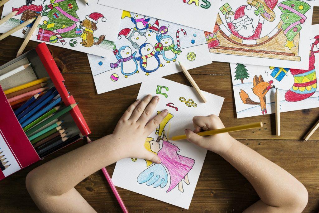 ребенок раскрашивает цветными карандашами раскраску