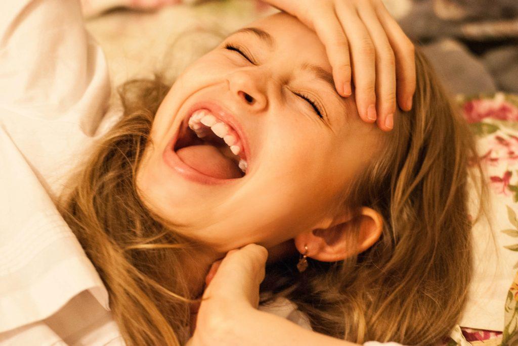 девочка держится за лоб и смеется истерическим смехом, гиперактивный ребенок
