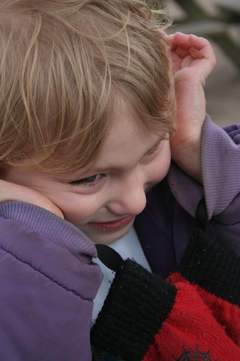 девочка улыбается, подведя руки к щекам