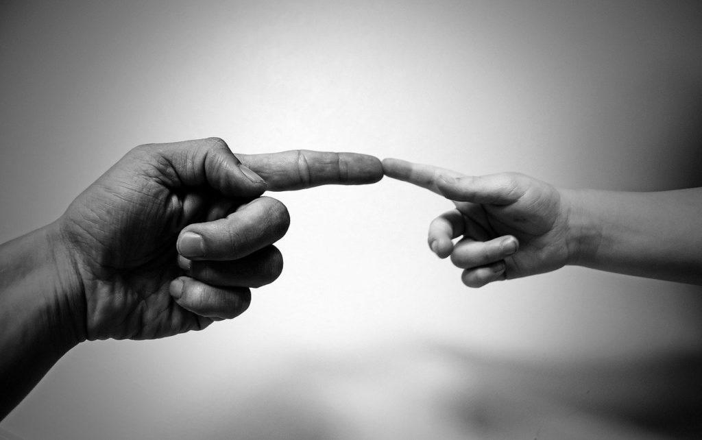 ребенок и мужчина касаются друг друга указательными пальцами
