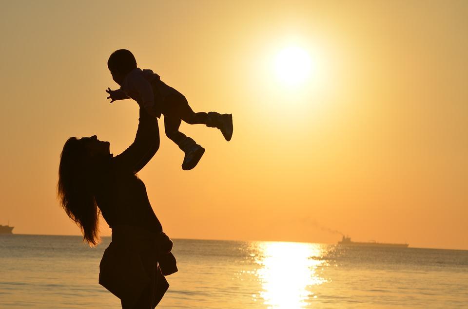 мама качает ребенка на берегу моря