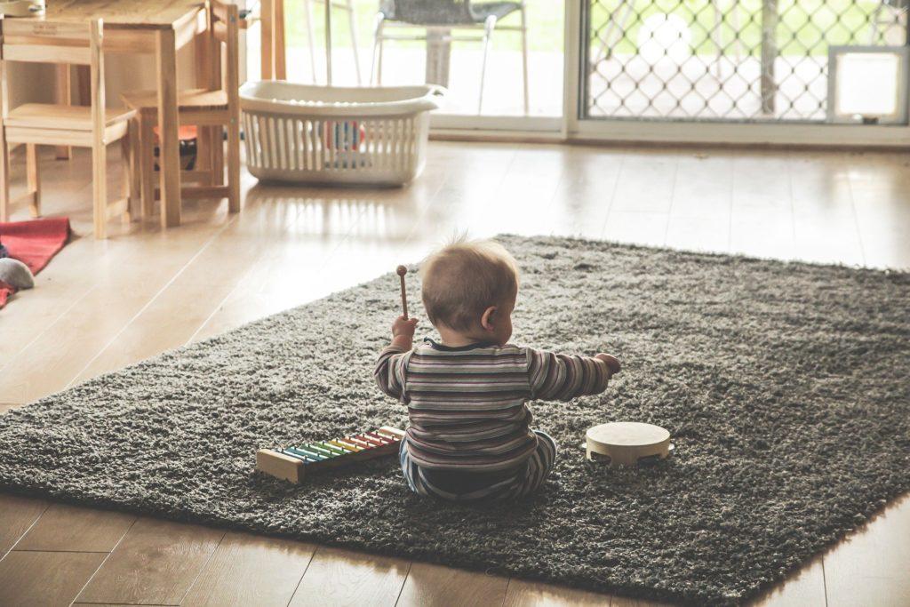 ребенок сидит на ковре и играет с игрушками в одиночестве
