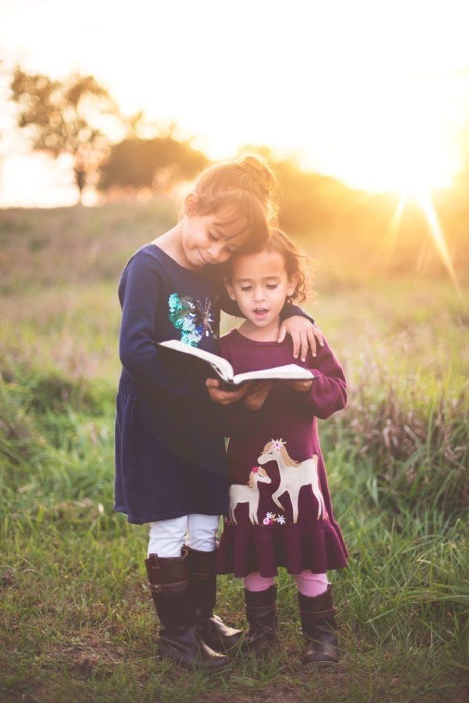 две девочки смотрят в книгу на природе