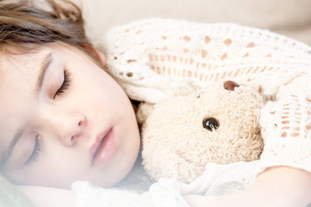 девочка спит с плюшевым медвежонком