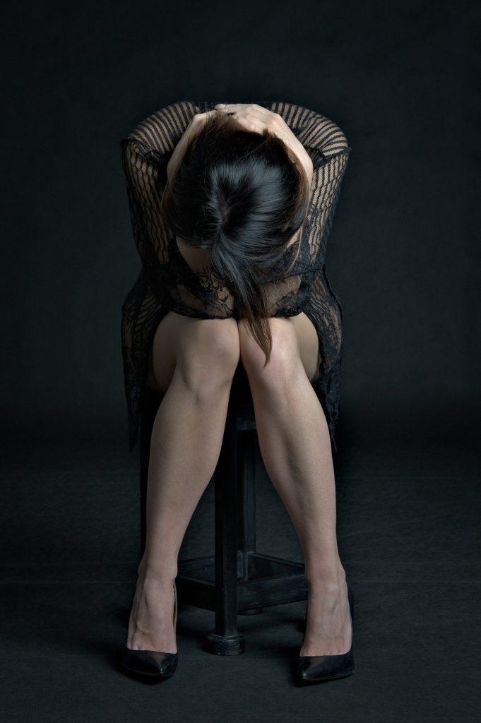 женщина сидит обхватив голову руками в печали