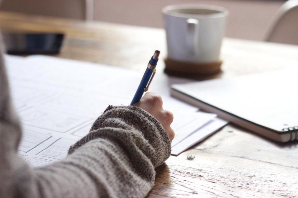 рабочий стол с тетрадью на столе, пишут ручкой