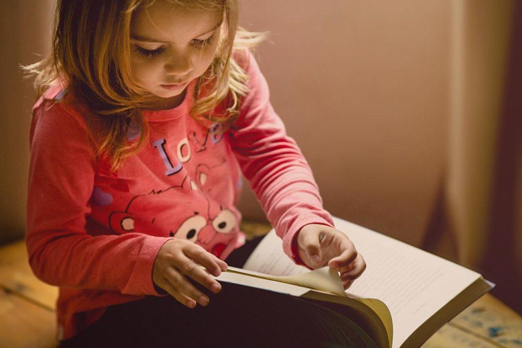 девочка в розовой кофте перелистывает на коленях большую книгу