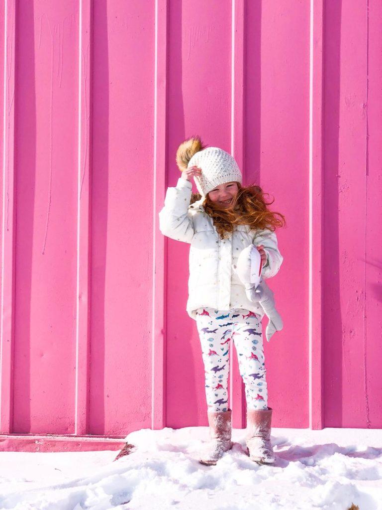 девочка стоит в снежную погоду с игрушкой в руках на фоне розовой стены