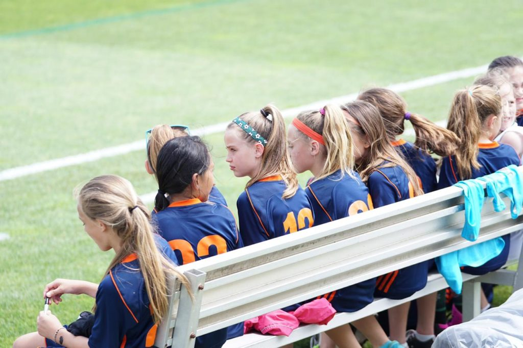 мотивация ребенка, команда девочек по футболу сидит на скамейке в спортивной форме